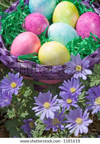 A basket of Easter eggs sits amid lovely purple spring flowers.