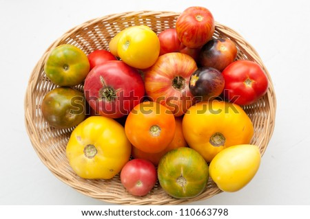 a basket of farm fresh heirloom tomatoes with many varietal kinds