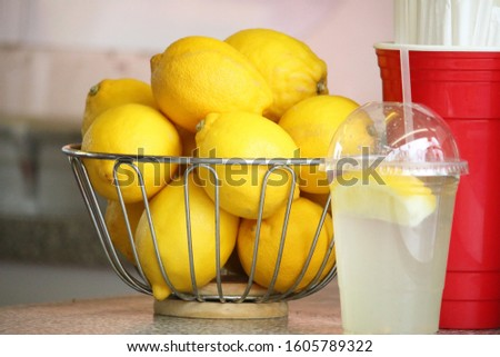 A basket of fresh lemons sits on a table with a freshly squeezed lemonade drink in a clear plastic cup next to it.