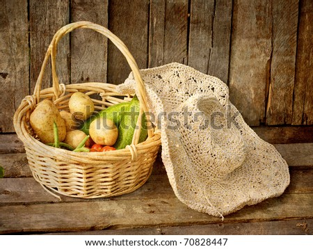A basket of fresh picked organic vegetables and a straw hat on a grunge wood background, textured.