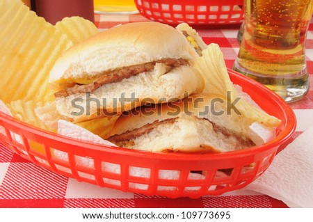 A basket of sliders, or mini cheeseburgers, and potato chips with beer