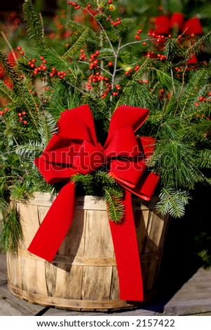 A basket with pine branches and bright red ribbon
