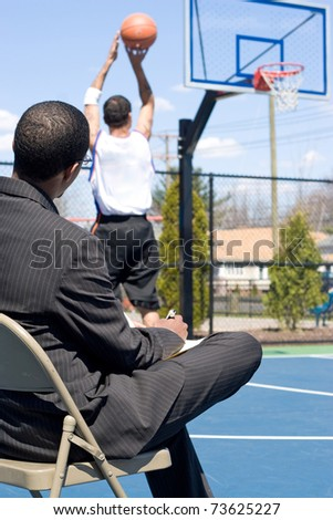 A basketball coach in a business suit observing a player on the team.   He could be also be recruiter trying to scout him.  Shallow depth of field.