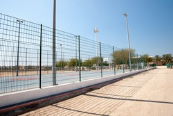 a basketball court fence against a blue sky with a sand path in the foreground
