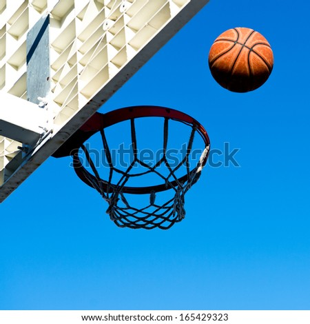 A basketball field goal with the sky in background.