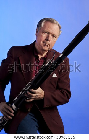 A bassoon musician performing against an isolated blue background with copy space in the vertical format. - stock photo