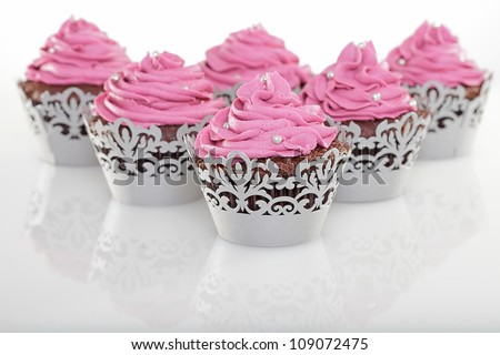 A batch of fancy chocolate cupcakes with pink icing.