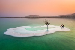 A bather relaxing on an island in the Dead Sea on a hazy morning