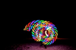 A baton show made of colorful LED lights with beautiful patterns that change as the lights twirling.