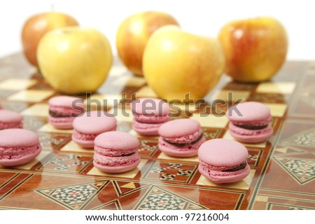 a battle between fresh apples and dessert macaroons. Represents conception of weight loss and healthy lifestyle