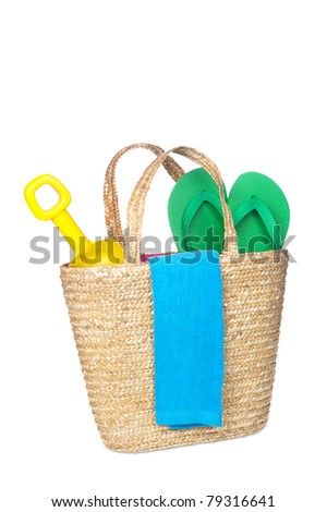 A beach bag carrying a toy shovel, flip flops and a beach towel.