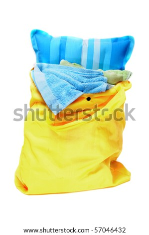 a beach bag, with towels and an inflatable pillow, on a white background