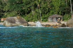 A beach front surf shack on a sandy beach with big rocks