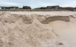 A beach on Fire Island with heavy erosion after the sand is washed away from a storm.
