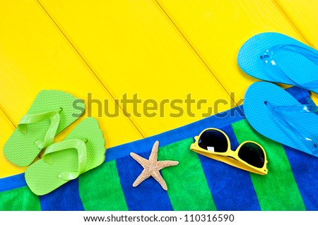 A beach towel, flip flops and sunglasses on a colorful yellow wooden deck with the presence of a starfish to insinuate a beach relates setting.