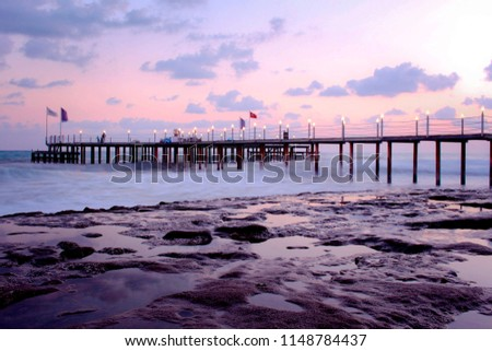 a beach with a pier in front of a sea at purple sunset #1148784437