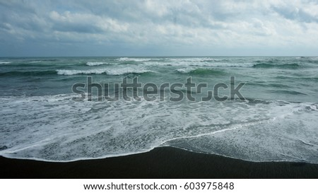 A beach with black sand. Turquoise ocean and black sand. Waves on the ocean, foamy white waves. Blue-green water spills over black sand #603975848