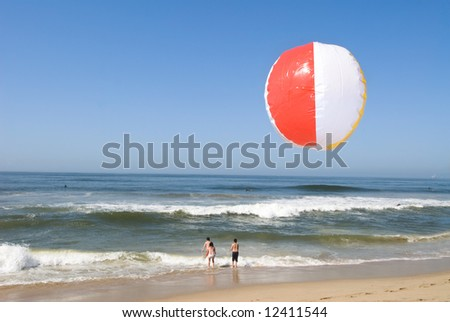 A beachball flys through the air at the beach while children in the surf beat the summer heat.