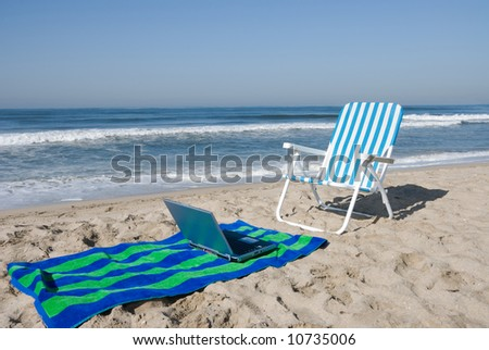 A beachfront office includes a laptop, chair and beach towel