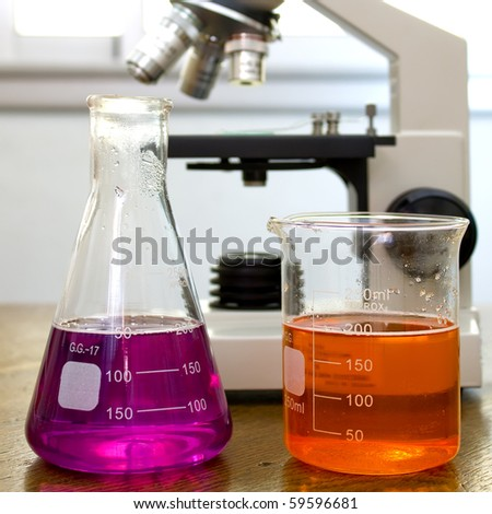a beaker and a flask with colorful substances inside. In the background is a microscope