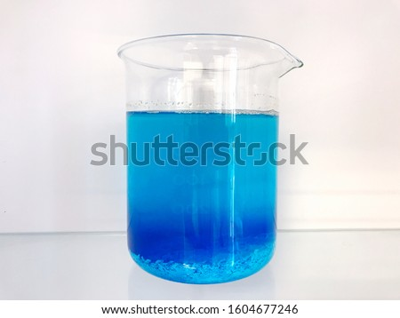 A beaker of chemical in laboratory. The chemical is copper II sulphate which is blue in color