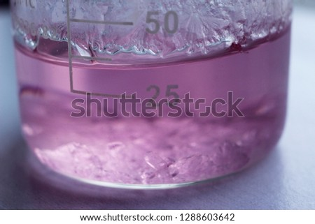 A beaker with a saturated solution of manganese sulphate. The process of salt crystallization began on the bottom and on the inner surface of the beaker. #1288603642
