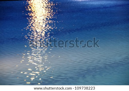 A beam of sunlight reflecting over rippled blue water with copyspace