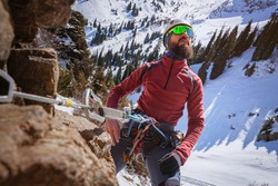 A bearded climber, strapped in with a safety device, takes a breath while admiring the landscape. Winter mountaineering. A man climbs a rock. Mountain climber portrait