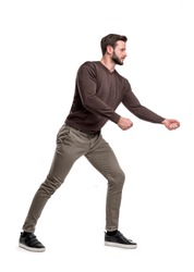A bearded man a casual wear tries to pull an invisible rope with all his force. Pull rope. Win over opponent. Tug of war.