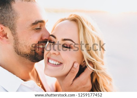 A bearded man and a blond woman are embraced and illuminated by a sunbeam. Closeup portrait of emotional people at sunset. Love in the desert newlyweds. The love story of merry and lovers young. #1259177452