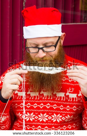A bearded man in a Christmas hat knits. Handmade Santa Claus, red sweater, jacket, warm clothes, a red beard, festive mood, new year, christmas concept