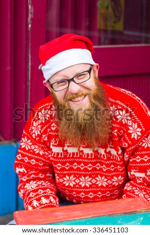 A bearded man in a Christmas hat knits. Santa Claus,red beard red sweater, smile and happy; warm clothes, festive mood, new year, christmas concept