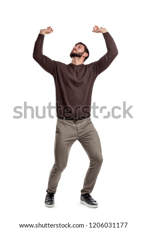 A bearded man in casual clothes attempts to hold something heavy from above on a white background. Heavy object. Lifting something up. Big burden.