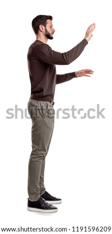 A bearded man in casual clothes stands still in a side view and used both hands to touch invisible digital screen. Digital panel. Using new technologies. Receiving data.