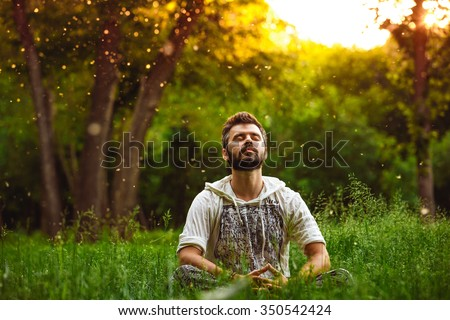 A bearded man is meditating on green grass in the park with face raised up to sky and eyes closed on sunny summer day. Concept of meditation, dreaming, wellbeing and healthy lifestyle Сток-фото ©