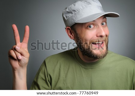 A bearded man wearing a cap to point the finger victory