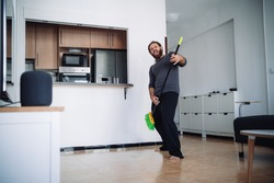 A bearded man wearing a pajama uses a sweep to simulate a guitar while brooms the floor of his living room while listening music from a smart speakers