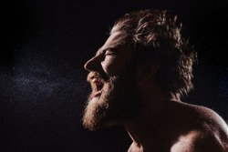 A bearded man without a shirt shouts in a spray of water against a black background. from the side view with copy space. portrait close up view