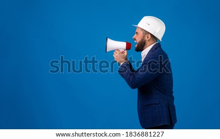 a bearded middle-aged construction worker in a suit and construction helmet speaks into a megaphone on a blue isolated background . a young architectural engineer shouts over a loudspeake. Photo stock ©