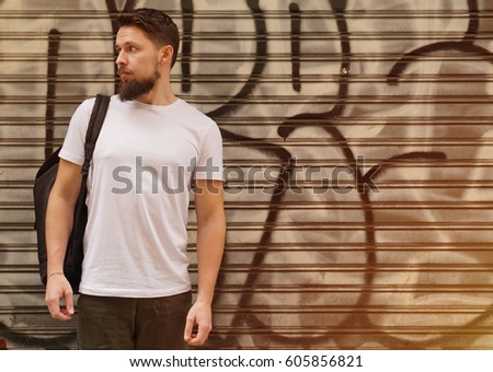 A bearded young man with a backpack wearing a white blank t-shirt and jeans standing on a graffiti wall background. Horizontal mock up. Stock fotó ©