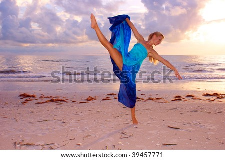 A beautiful adult female ballerina is dancing on the beach with her leg kicked up high and balanced on one foot as the sun begins to set - stock photo