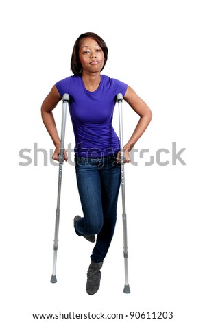 A beautiful African American black woman using a set of medical crutches to help her walk - stock photo
