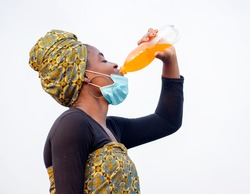 A beautiful African lady drinking a yellow liquid content from a transparent bottle with her nose mask below her jaw
