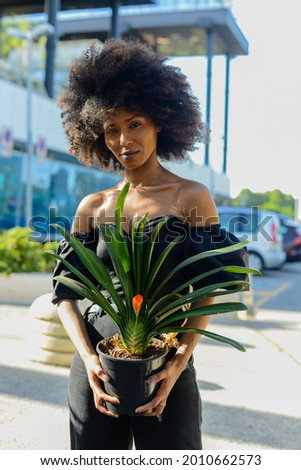 A beautiful Afroamerican female holding a pot of Clivia plant on background of an urban building Stock photo ©