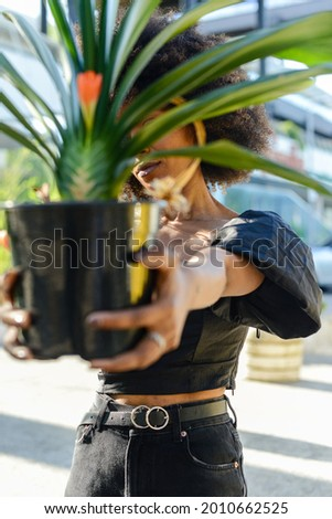 A beautiful Afroamerican female showing a pot of Clivia plant on background of an urban building Stock photo ©