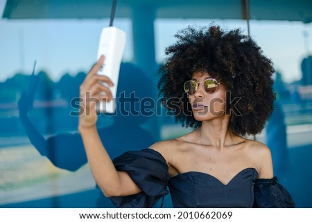 A beautiful Afroamerican female taking a selfie on a modern retro style phone on background of window Stock photo ©