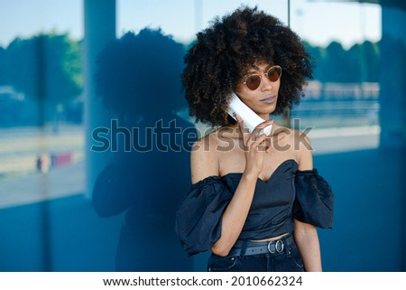 A beautiful Afroamerican female talking on a retro phone on background of a modern building Stock photo ©