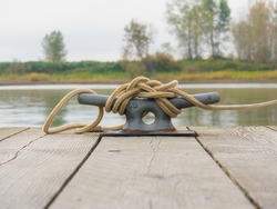 A beautiful aged dock cleat anvil with rust, rustic vintage look on wood plank of dock.