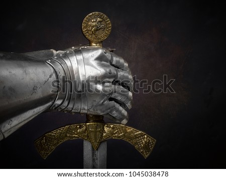A beautiful ancient sword of the Order of the Knights Templar and an iron knight's glove on a dark beautiful background.