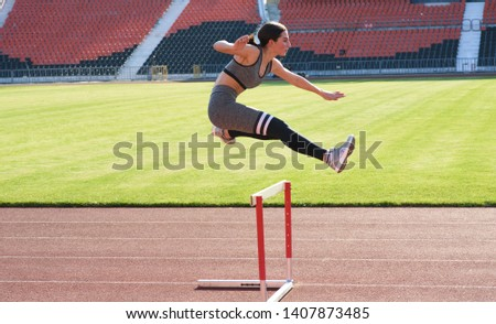 A beautiful and athletic girl is running hurdles in the stadium